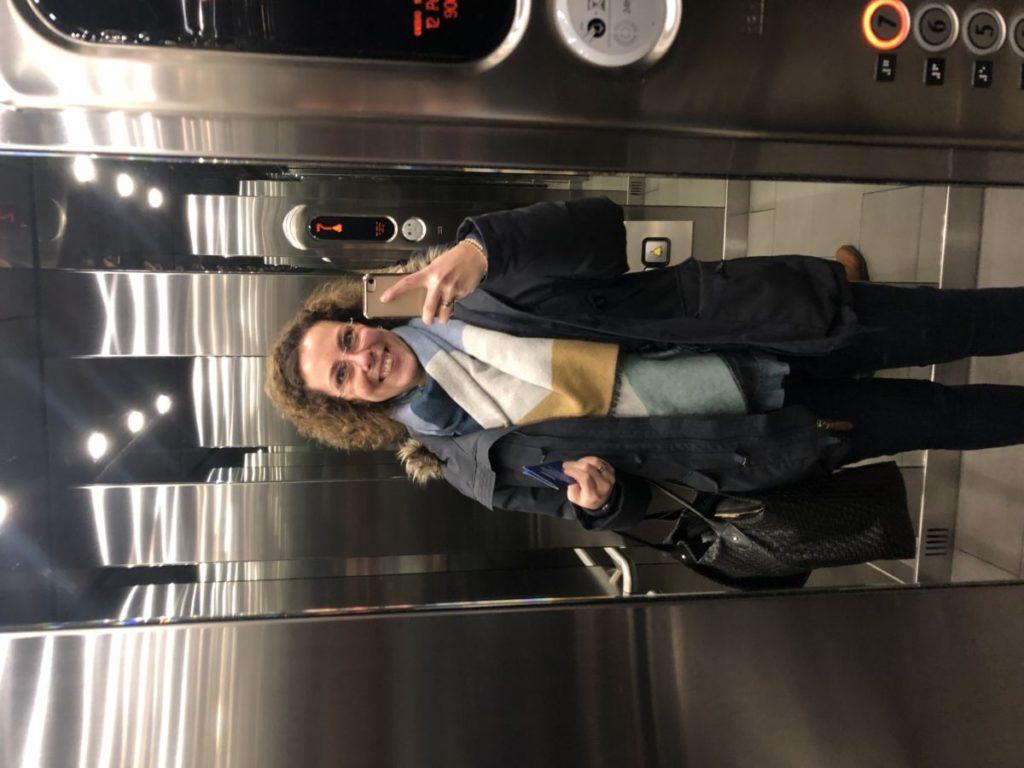 Louise i hissen på hotell. Vinterjacka, väska på axeln.