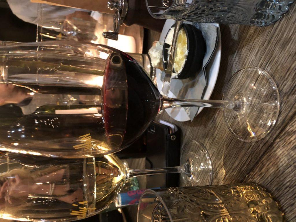 Ett glas med rött vin på ett bord med många glas vin