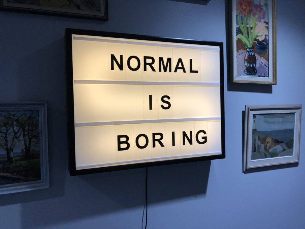 Ljusbild med text på: Normal is boring