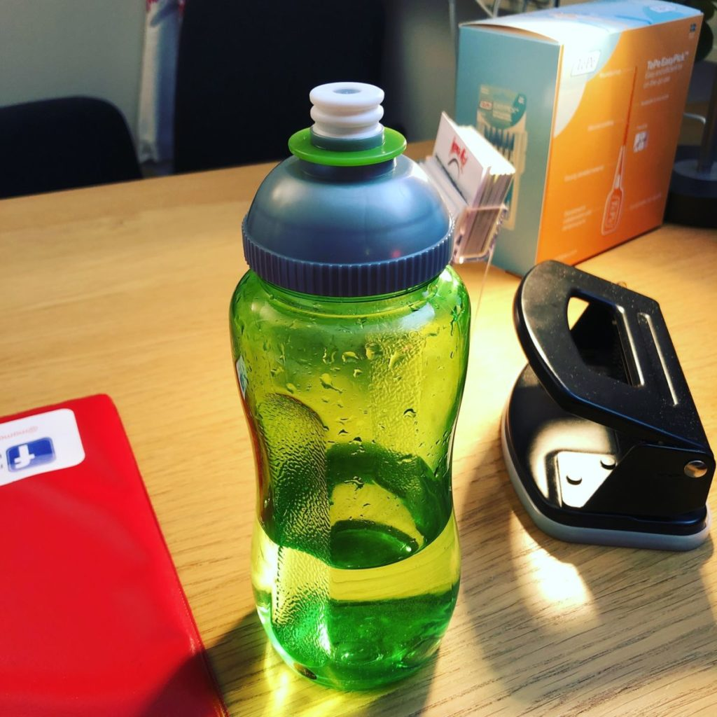 Gör vattenflaska på skrivbord, en hålslagare syns i bakgrunden