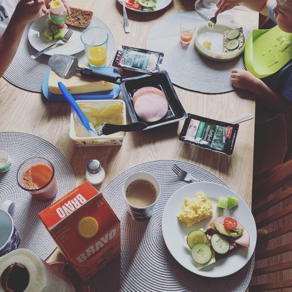 frukostbord uppifrån med jucice, smörgåsas, ost, skinka med mera