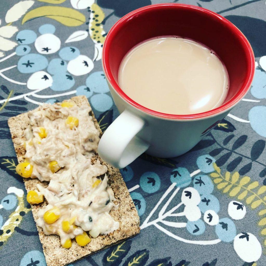 Knäckebröd med tonfiskröra och en kopp kaffe på en mönstrad duk
