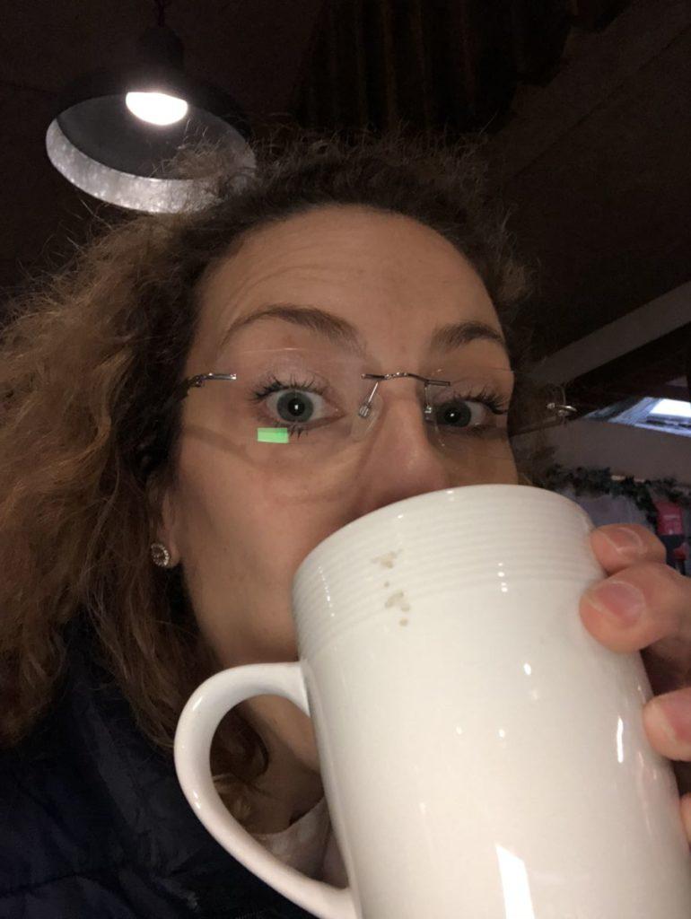 Louise dricker kaffe ut vit mugg