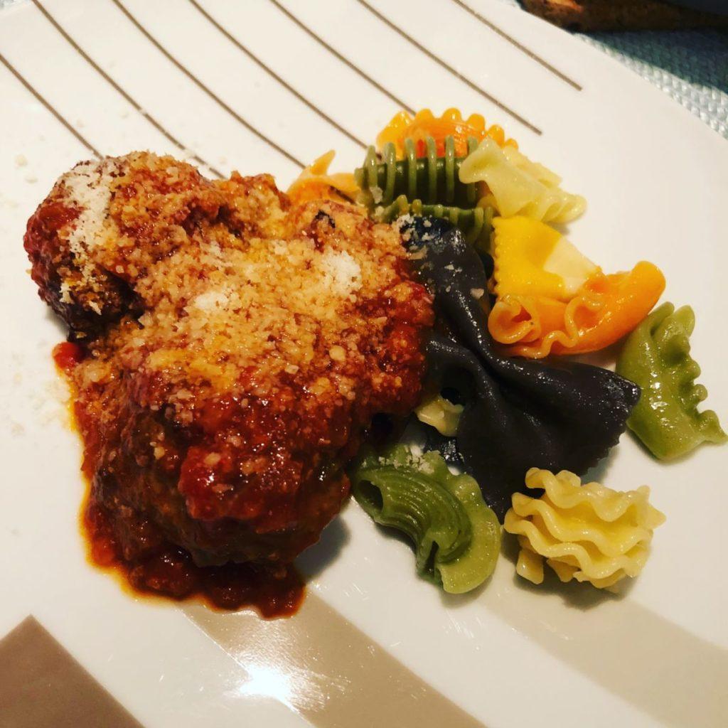 Färgglad pasta på vit tallrik med streck. Köttbullar i tomatsås.