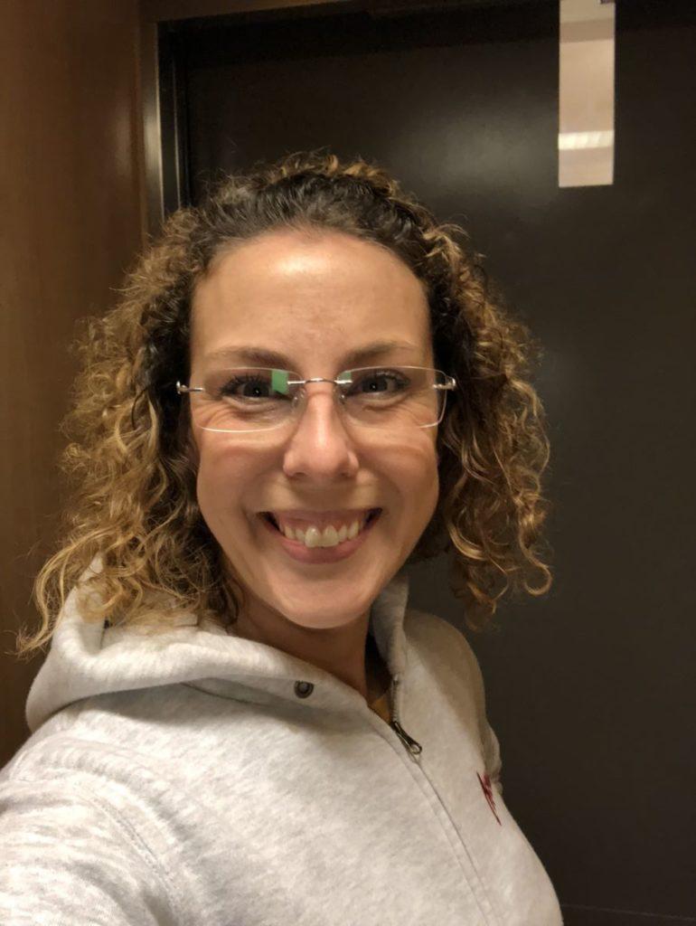 Louise selfie med grå bakgrund. Har ljusgrå luvtröja på sig.