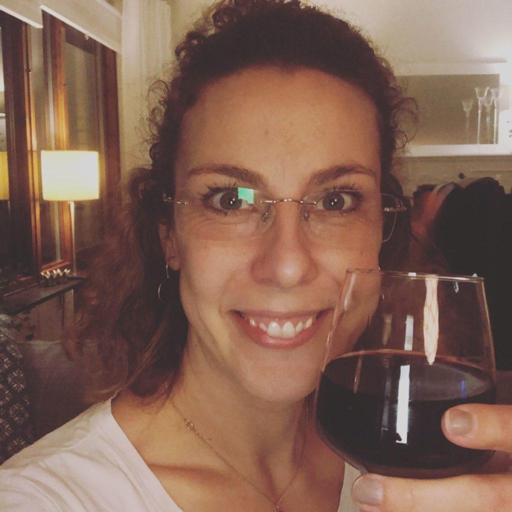 Louise skålar med kameran i ett glas rött vin.