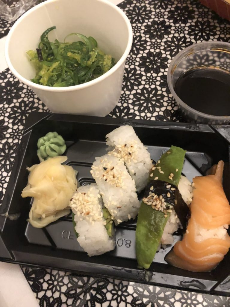 En skål med grön sjögrässallad och fem sushibitar med ingefära och wasabi