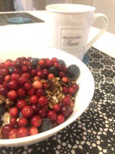 Frukostskål i vitt med naturell yoghurt, hemgjord granola och färska lingon och blåbär på samt en vit kopp med kaffe till