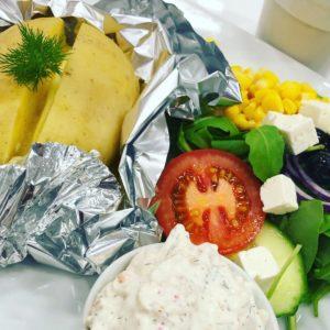 Bakad potatis i folie meddillkvist på, sallad med tomat, majs, gurka och tomat samt en liten skål med skagenröra i