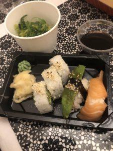 Plastfat med 5 st sushibitar, inlagd ingefära och wasabi samt sjögrässallad i en liten skål bredvid och soja till