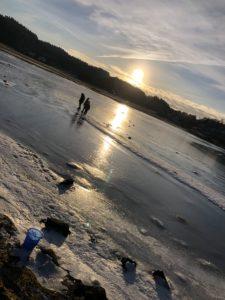Foto vid stranden med is på vattnet, strålande solsken och frostigt runt omkring