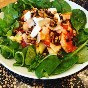 En assiett med grön färsk bladspenat och pasta, kyckling med parmesanskivor och rostade pinjenötter ovanpå