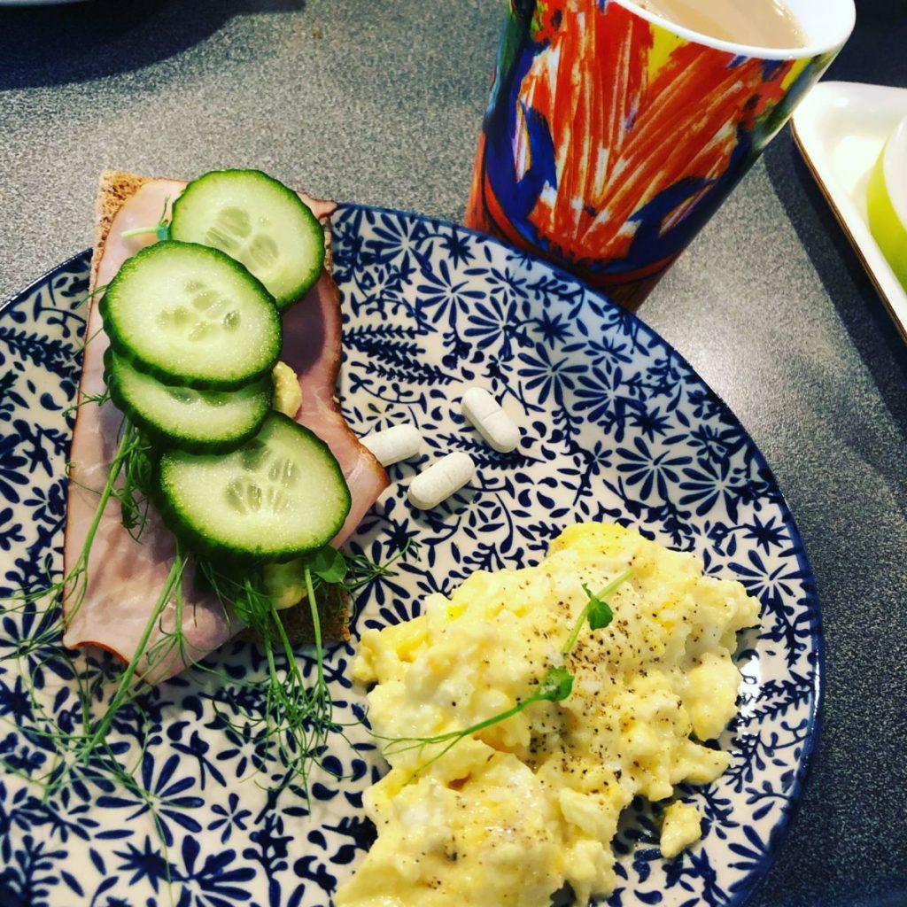 Blåvit tallrik med smörgås, äggröra och tre tabletter på. Kaffemugg bredvid, orangemönstrad