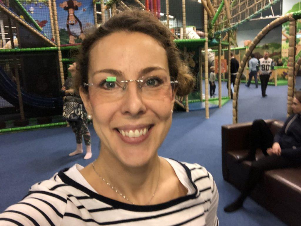 Bild på Louise i randig tröja, uppsatt hår, glasögon, lekställning i bakgrunden