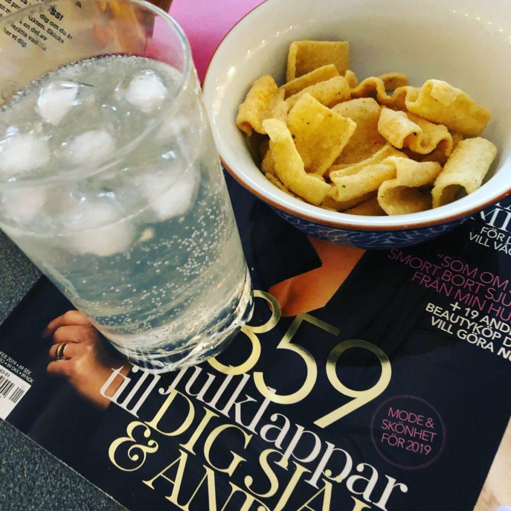 Ett glas med genomskinlig dryck, is. En skål m chips. Allt står på en tidning