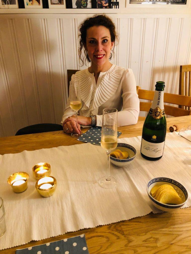 Louise i bakgrunden. Champagneflaska och glas i förgrunden