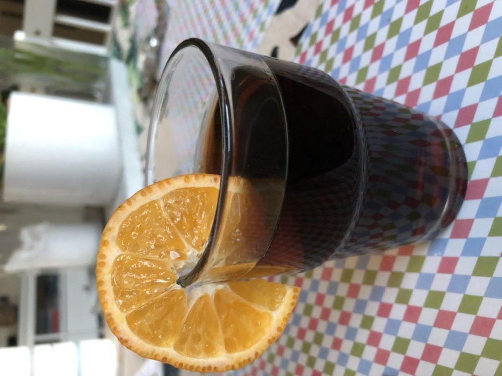 En litet glas med brun dryck. En skiva apelsin på glaskanten