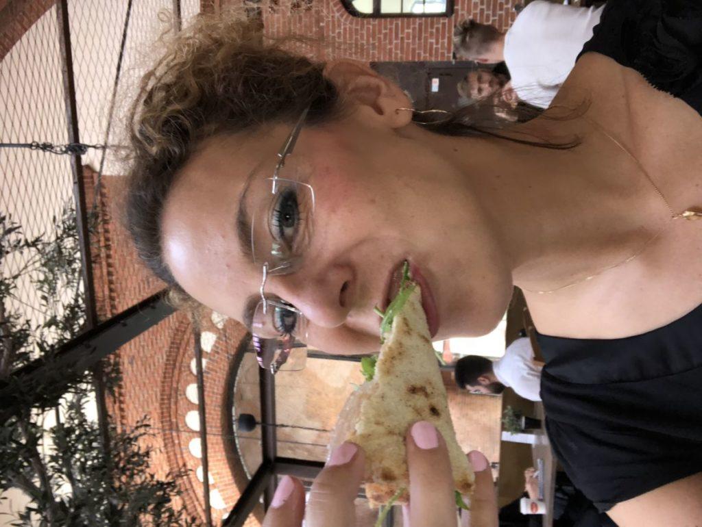 Louise från sidan har en pizzaslice i munnen