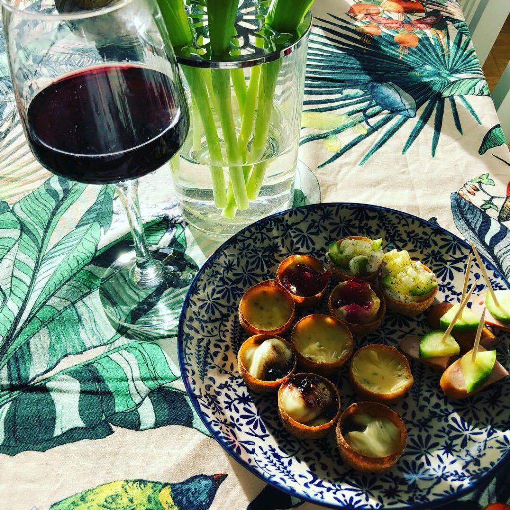 En glas rött vin med en tallrik med små plocksaker på