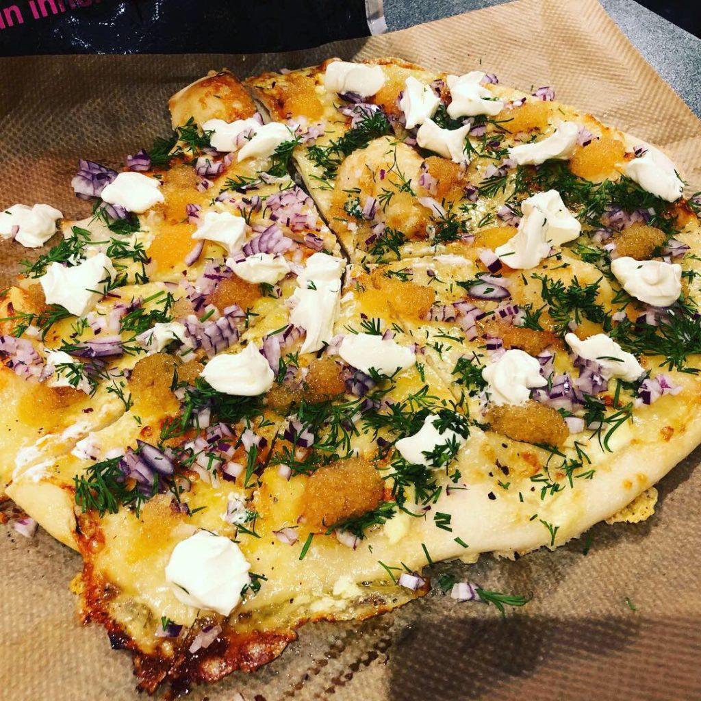 Pizza på bakplåtspapper med löjrom, dill, rödlök och creme fraiche