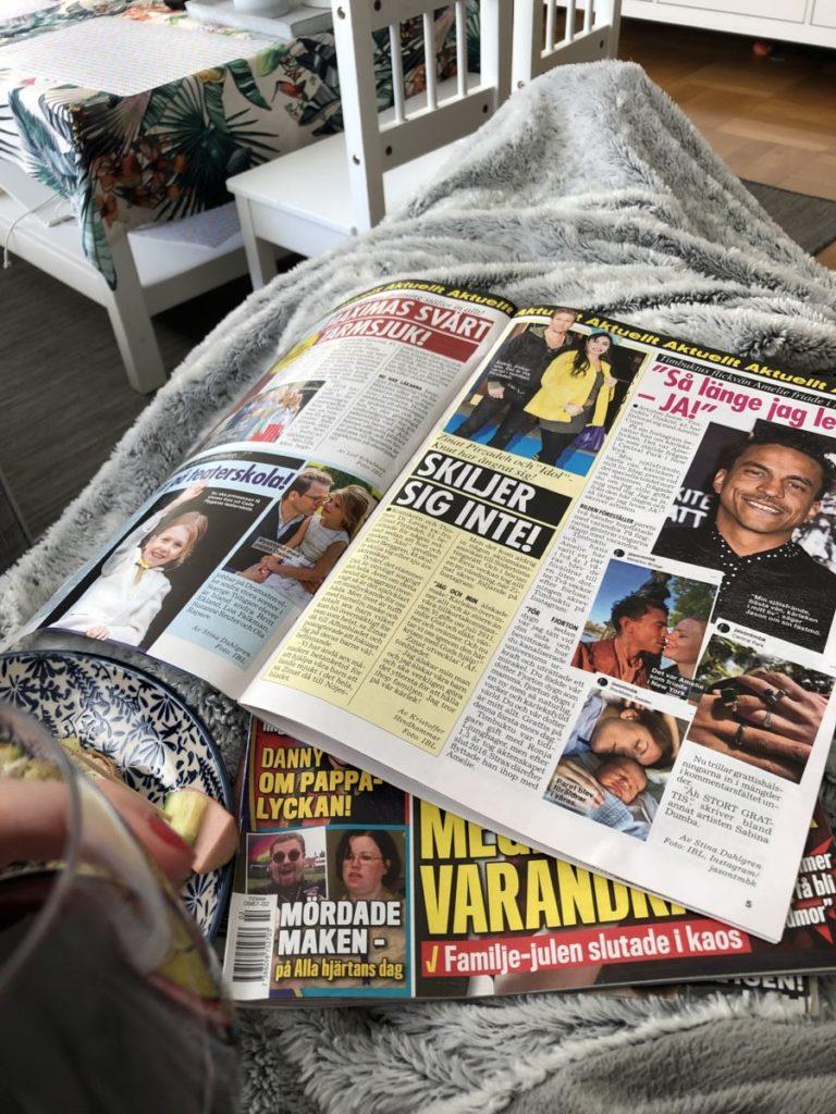 flera färgglada uppslagna tidningar i ett knä