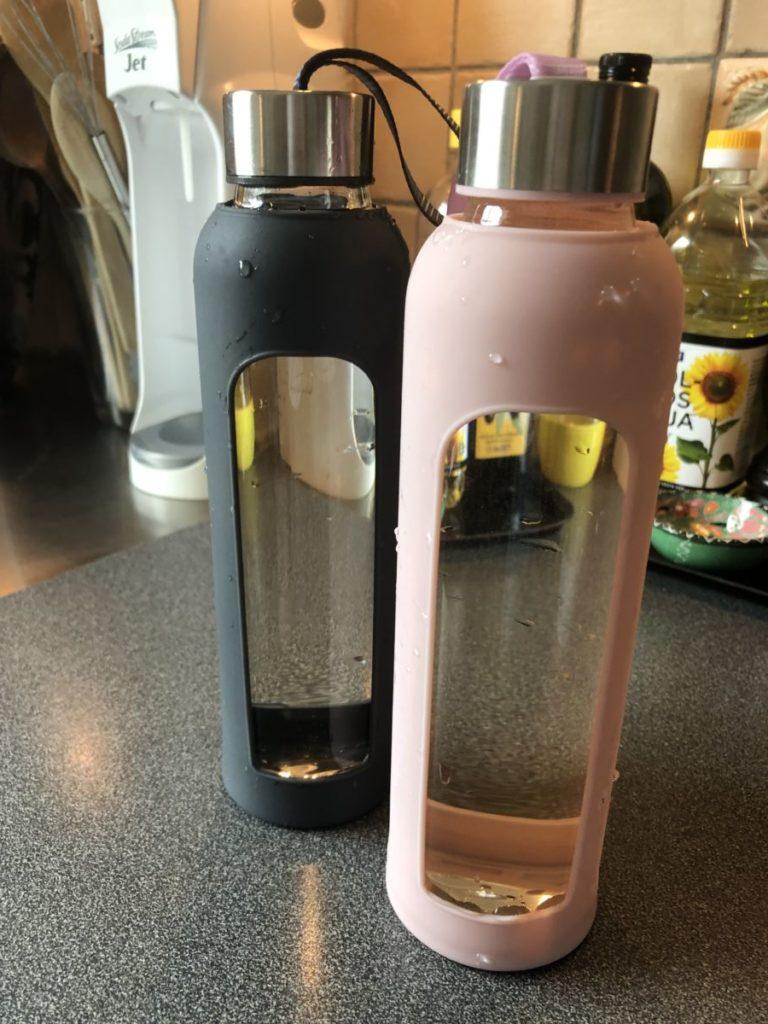 Tv å flaskor med silikonomhöje, en grå och en ljusrosa