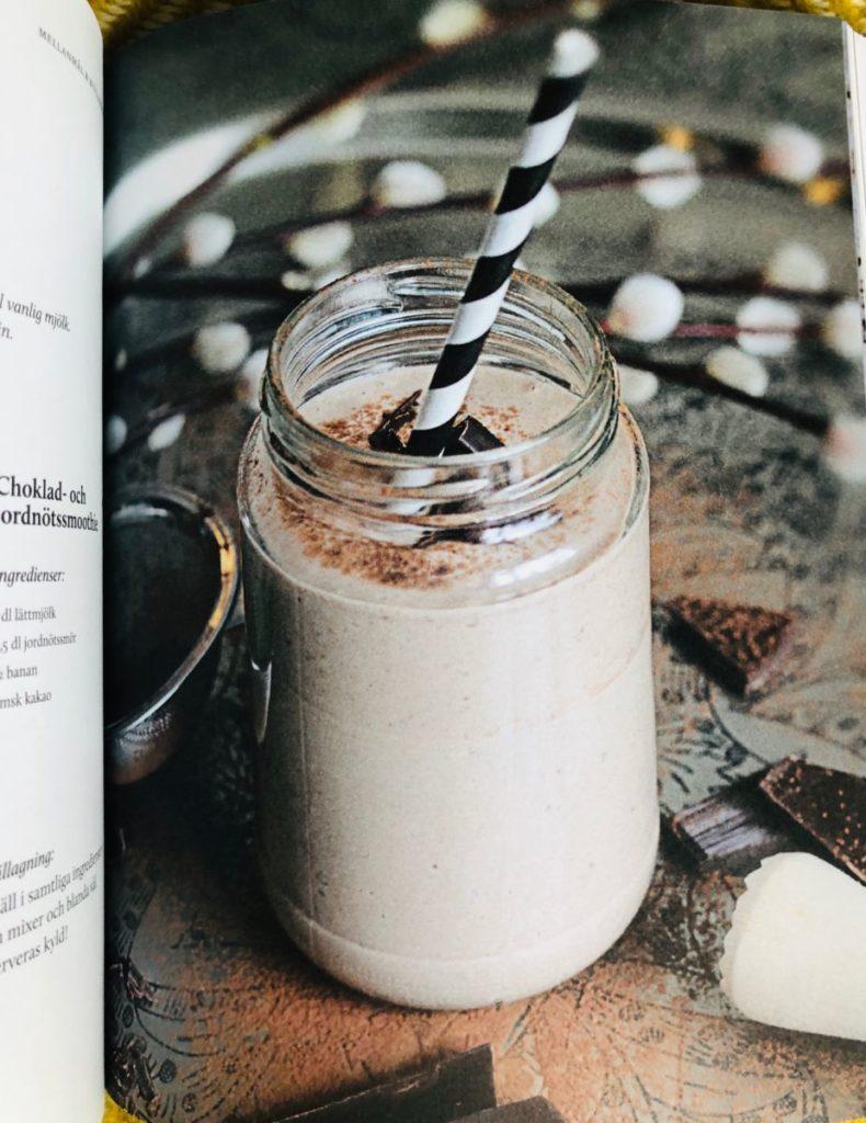 Glas med ljusbrun smoothie och svartvitt sugrör