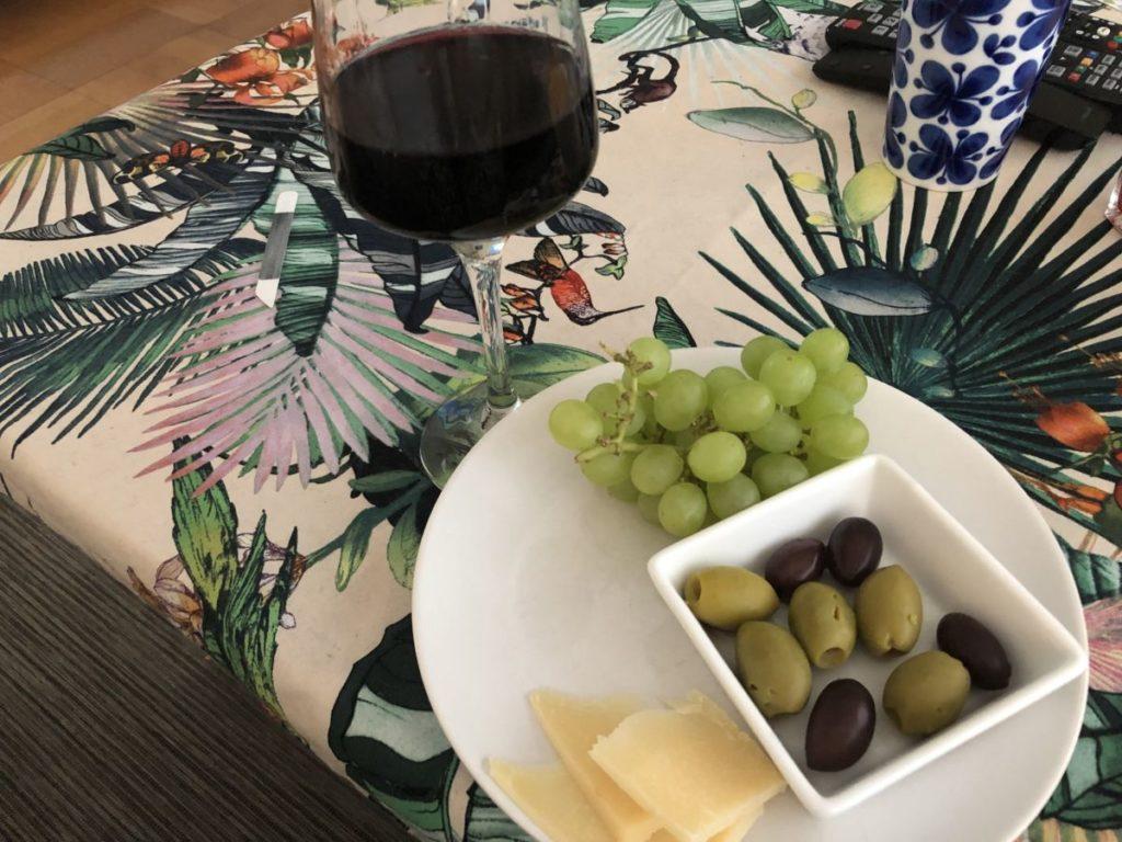 Mönstrad duk, ett glas vin, vit tallrik med ost, oliver och druvor på
