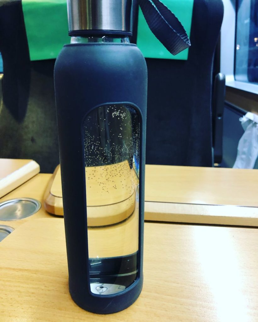 Glasflaska m grått silikonskal. Tågkupé i bakgrunden