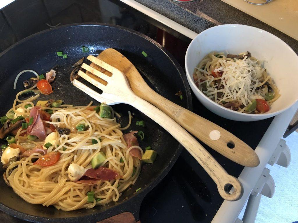 stekpanna med spagetti och grönsaker, en vit skål bredvid