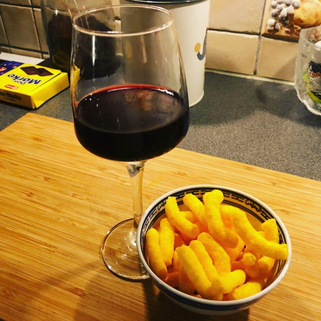 ett glas rött vin med en liten skål med ostbågar