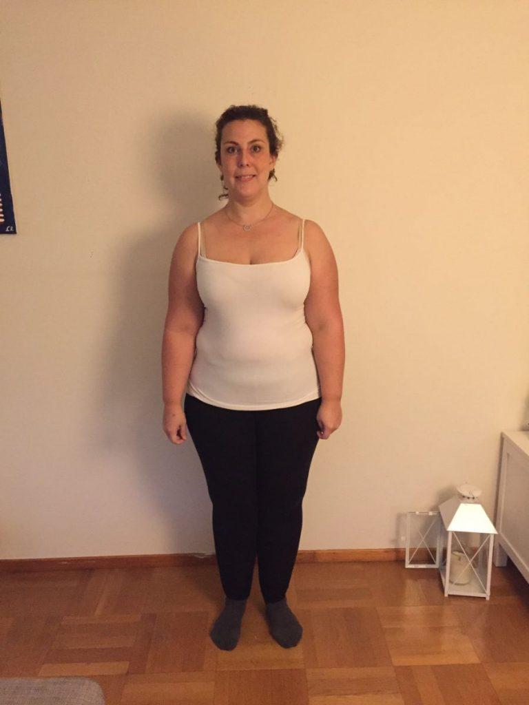 Louise mot vit vägg, vitt linne och svarta tights