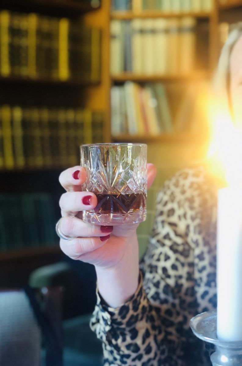 Kvinnohand håller i whiskyglas