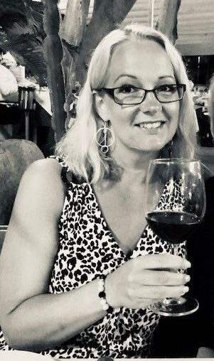 Svartvit bild på Sophia med ett glas rött vin